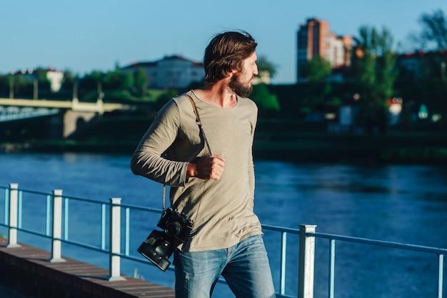 Modny fotograf spacerujący po mieście z retro aparatem fotograficznym