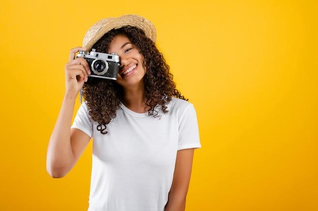 Modny hipster czarna dziewczyna z rocznika kamery i kapelusz na białym tle nad żółtym
