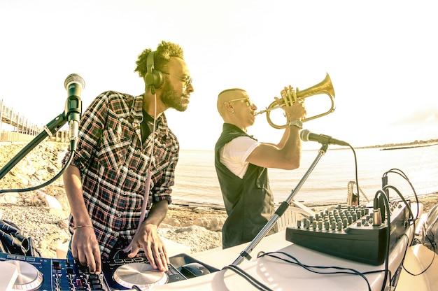 Modny hipster dj grający letnie hity na imprezie o zachodzie słońca na plaży z wykonawcą jazzu na trąbce