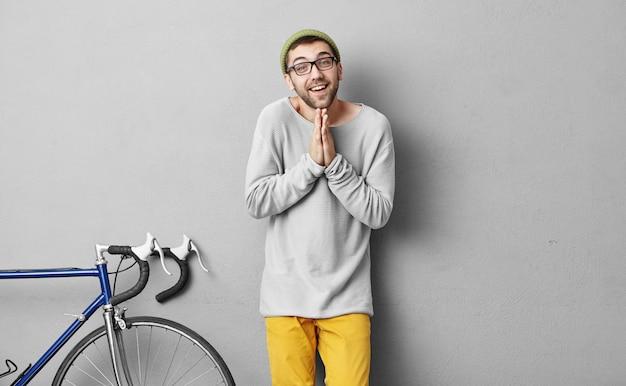 Modny hipster facet błaga o coś stojąc w pobliżu roweru. młody sportowiec będzie ścigał się na rowerze, trzymając dłonie razem i prosząc o chwilę odczekania