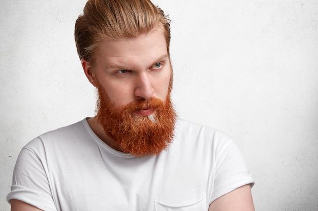 Modny hipster facet ze stylową fryzurą, gęstą rudą brodą i wąsami, patrzy poważnie i pewnie na odległość, kontempluje coś