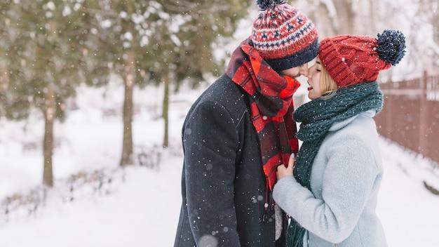 Modny kochający pary całowanie w opadzie śniegu