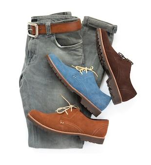 Modny koncept, odzież męska w innym kolorze butów, szare dżinsy i skórzana pasek na białym tle. widok z góry