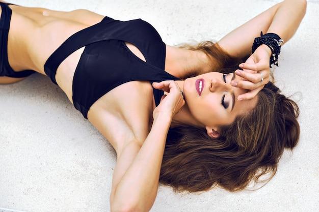 Modny letni portret pięknej brunetki leżał na podłodze, ubrany w modne, niezwykłe minimalistyczne bikini i jasny makijaż