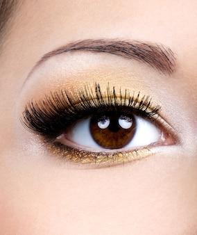 Modny makijaż oczu ze złotym cieniem do powiek - sesja makro