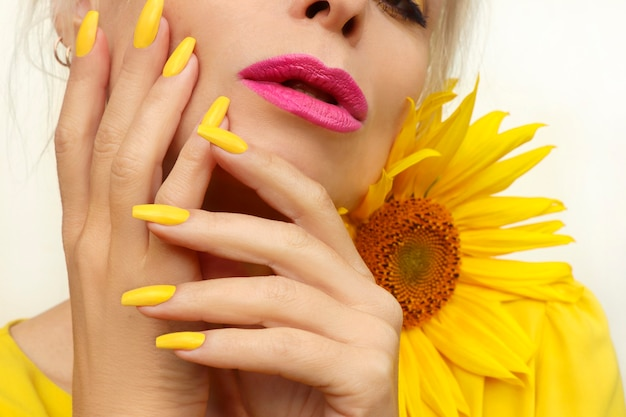 Modny manicure na długich paznokciach pokrytych żółtym lakierem na kobiecie z różowymi ustami.