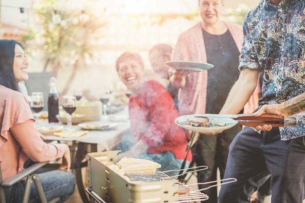 Modny mężczyzna gotowania i serwowania mięsa na kolację z grilla na świeżym powietrzu