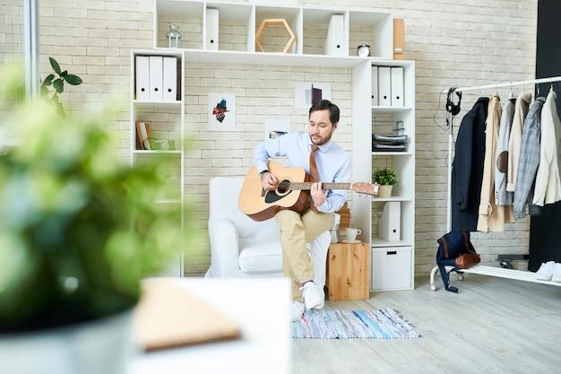 Modny mężczyzna gra na gitarze w studio