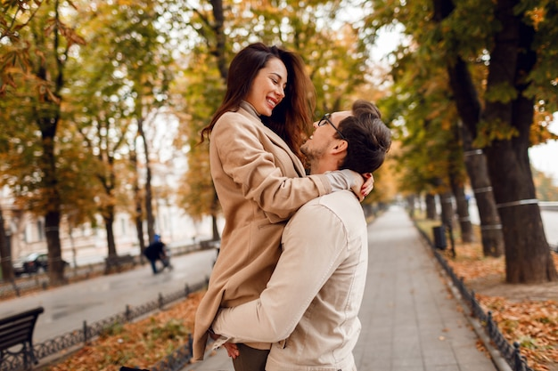 Modny mężczyzna i kobieta zawstydzający podczas randkowania w jesiennym parku. nosi stylowe beżowe płaszcze. romantyczny nastrój.