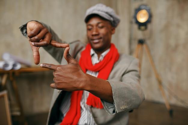Modny mężczyzna malarz w kapeluszu i czerwonym szaliku pokazuje znak ostrości, studio artystyczne. artysta rysuje w swoim miejscu pracy, twórczy mistrz pracuje w warsztacie