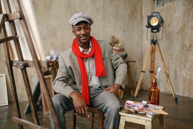 Modny mężczyzna malarz w kapeluszu i czerwonym szaliku pozuje przy sztalugach w pracowni artystycznej. artysta rysuje w swoim miejscu pracy, twórczy mistrz pracuje w warsztacie
