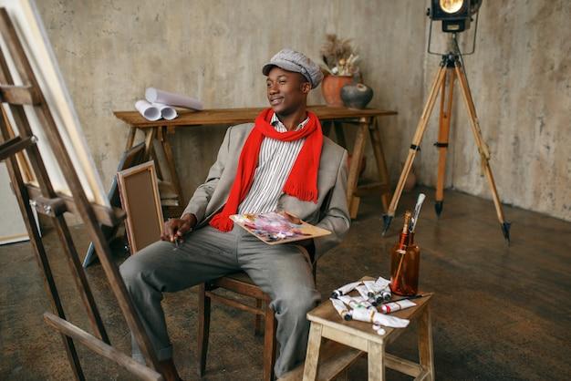 Modny mężczyzna malarz w kapeluszu i czerwonym szaliku, studio artystyczne. artysta rysuje w swoim miejscu pracy, twórczy mistrz pracuje w warsztacie