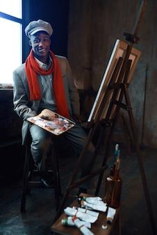 Modny mężczyzna malarz z paletą pozuje na sztalugach w pracowni artystycznej. artysta rysuje w swoim miejscu pracy, twórczy mistrz pracuje w warsztacie