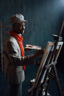 Modny mężczyzna malarz z paletą pozuje na sztalugach w pracowni artystycznej. artysta rysuje w swoim miejscu pracy