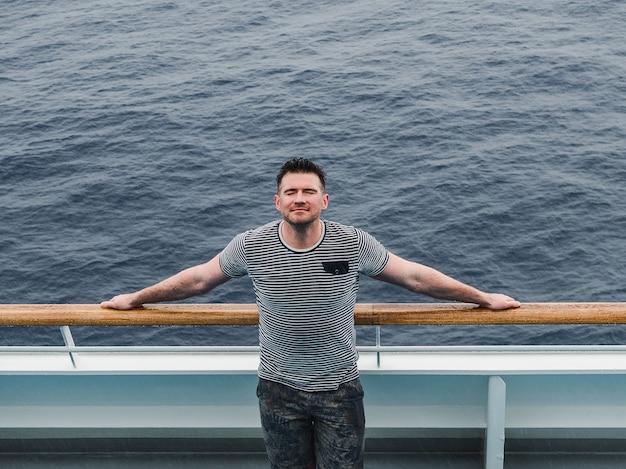 Modny mężczyzna na pustym pokładzie wycieczkowca na tle morskich fal.