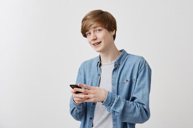 Modny mężczyzna o jasnych włosach i niebieskich oczach w dżinsowej koszuli pozuje w pomieszczeniu za pomocą telefonu komórkowego, rozmawia z przyjaciółmi, pisze wiadomość. sprytny student wykorzystujący nowoczesne technologie, z uśmiechem