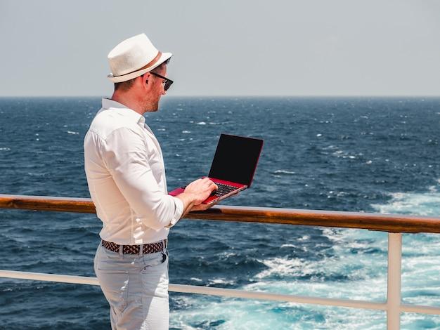 Modny mężczyzna, pracujący na czerwonym laptopie