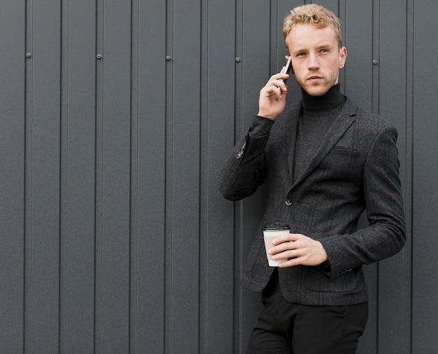 Modny mężczyzna rozmawia przez telefon z kawą