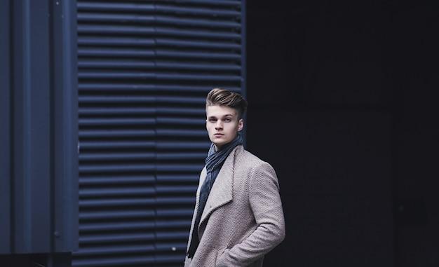 Modny mężczyzna stoi na ulicy w płaszczu. zimowy, jesienny strój.