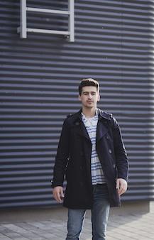 Modny mężczyzna stoi na ulicy. wiosenno-jesienny strój.