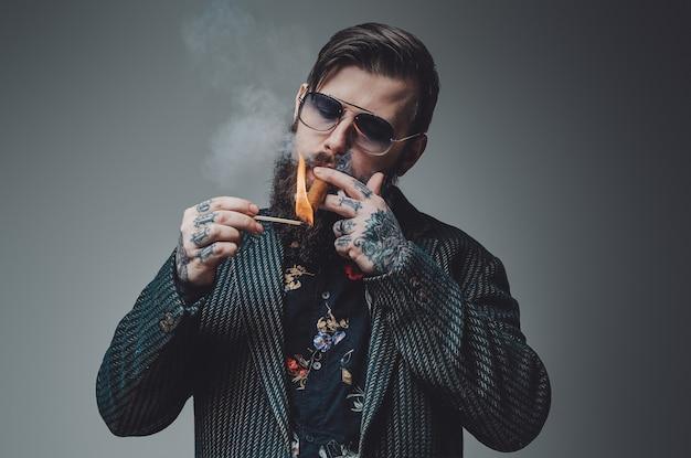 Modny mężczyzna ubrany w drogi garnitur stawia w szarym tle palenie elitarnych cygar kubańskich. wytatuowany i elegancki hipster.