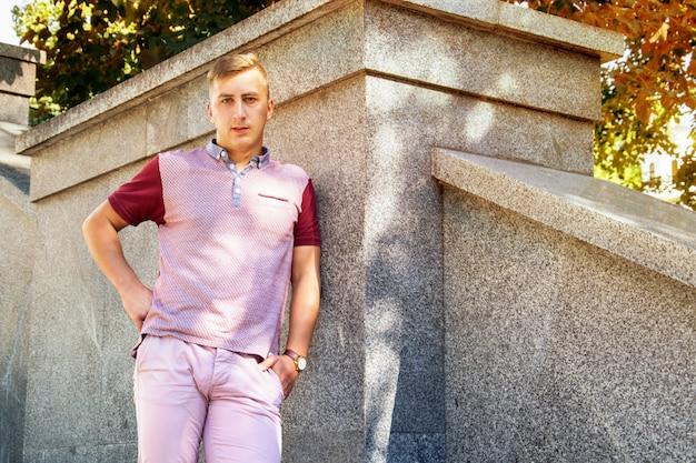 Modny mężczyzna w beżowych spodniach na kamiennej ścianie