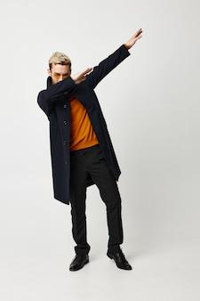 Modny mężczyzna w czarnym płaszczu, gestykulując rękami w nowoczesnym stylu