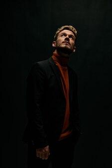 Modny mężczyzna w kurtce i swetrze patrząc na ciemnym tle. zdjęcie wysokiej jakości