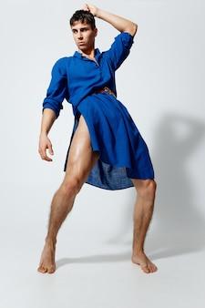 Modny mężczyzna w niebieskiej sukience tańczy na jasnym tle wesoły