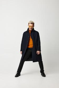 Modny mężczyzna w płaszczu rozłożył nogi na jasnym tle i pomarańczowe spodnie sweterkowe buty