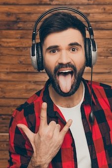 Modny mężczyzna w słuchawkach pokazujący rockowy gest i język