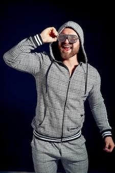 Modny mężczyzna w stylowym sportowym garniturze i okularach przeciwsłonecznych