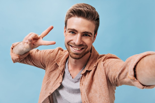 Modny mężczyzna z fajną brodą w szarej koszulce i brązowej koszuli robi zdjęcie i pokazuje znak pokoju na izolowanej niebieskiej ścianie
