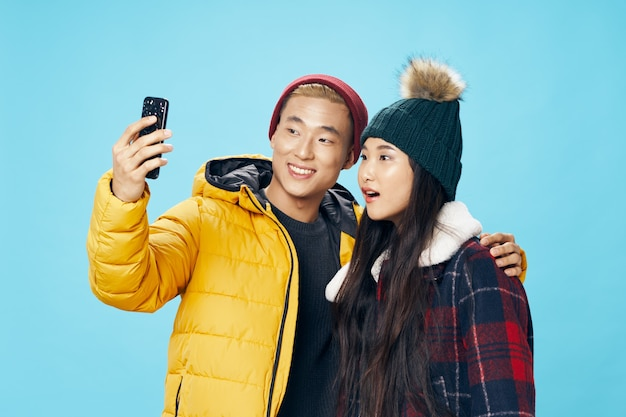 Modny mężczyzna z telefonem komórkowym i zdziwioną azjatycką kobietą na niebieskim tle w ciepłych ubraniach