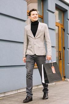 Modny młody człowiek gospodarstwa torba na zakupy z tagiem sprzedaż