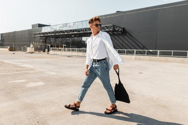 Modny młody człowiek hipster w stylowych białych i dżinsowych ubraniach w klasycznych sandałach z czarną płócienną torbą spaceruje na świeżym powietrzu w słoneczny dzień.