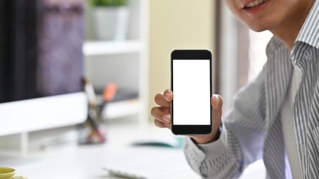 Modny młody człowiek pokazuje pustego ekran jego telefon komórkowy