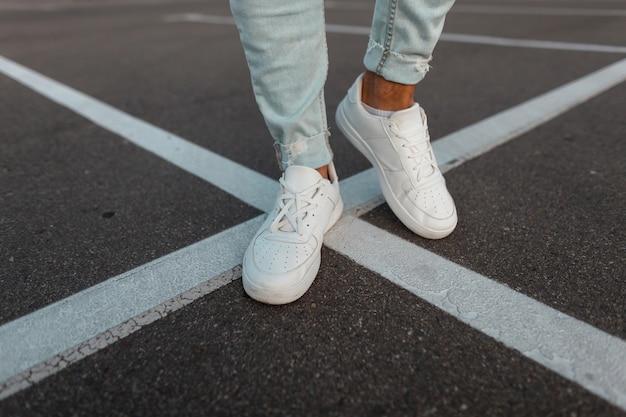 . modny młody człowiek stoi na asfaltowej drodze w skórzane stylowe białe trampki w modnych niebieskich dżinsach.