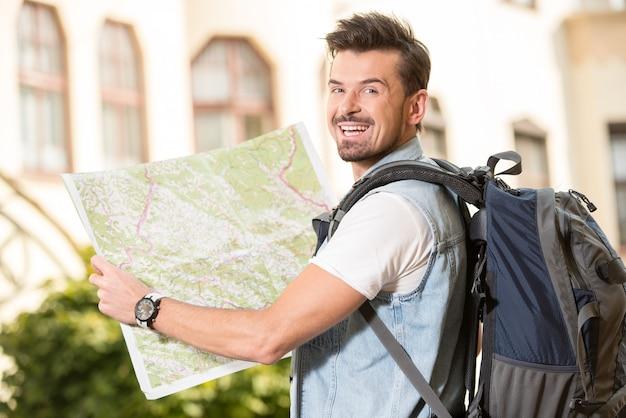 Modny młody człowiek w mieście z mapą turystyczną.