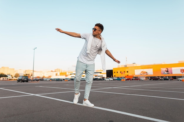 Modny młody człowiek w stylowe letnie ubrania w zabytkowych okularach przeciwsłonecznych w trampkach spacery po parkingu.