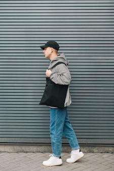 Modny młody człowiek w stylowej streetwear chodzącej z eko torbą na ramionach