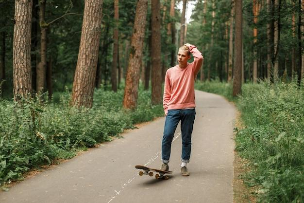 Modny młody człowiek z deskorolką w parku
