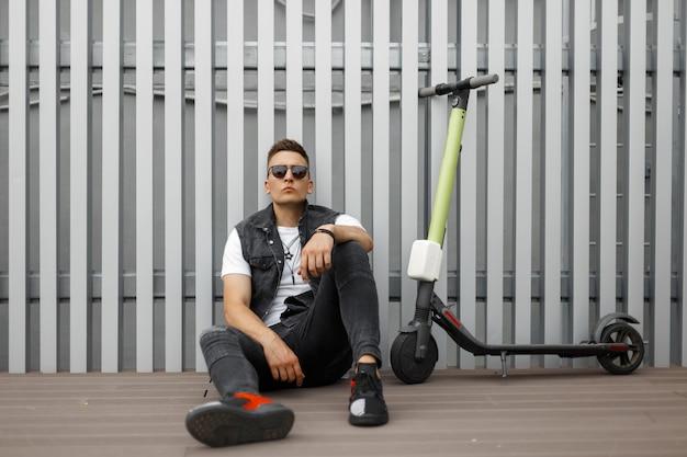 Modny młody hipster mężczyzna w kamizelce dżinsowej vintage w szarych dżinsach w trampkach w okularach przeciwsłonecznych spoczywa na drewnianej podłodze w pobliżu szarej ściany
