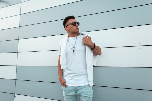 Modny młody hipster mężczyzna z modną fryzurą w okularach przeciwsłonecznych w dżinsach w białej koszulce pozuje w pobliżu nowoczesnego budynku