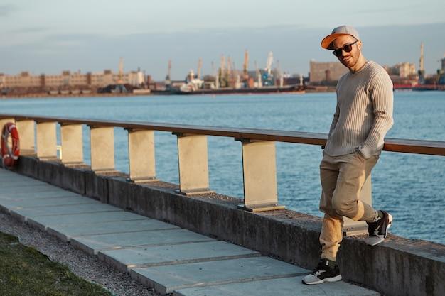 Modny młody mężczyzna pochylony w okularach przeciwsłonecznych, snapback i trampkach
