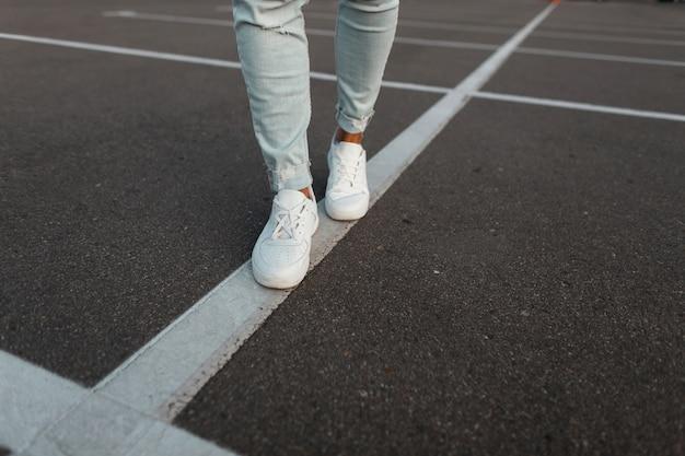 Modny młody mężczyzna w białych skórzanych trampkach vintage w modnych niebieskich dżinsowych spodniach. stylowe męskie buty letnie. swobodny design. zbliżenie męskich nóg.