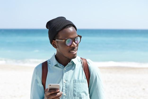 Modny młody turysta w okularach przeciwsłonecznych i kapeluszu po porannym spacerze wzdłuż wybrzeża morskiego