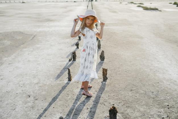 Modny model małej dziewczynki ubrany w białą letnią sukienkę trzyma brzegi kapelusza