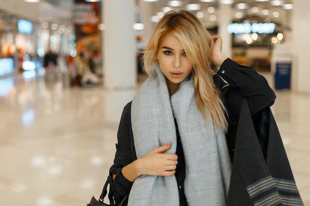 Modny model młodej kobiety w modnym płaszczu z szalikiem i torebką w centrum handlowym