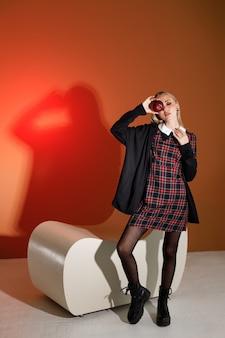 Modny model w jesiennych ubraniach z czerwonym jabłkiem w studio mody